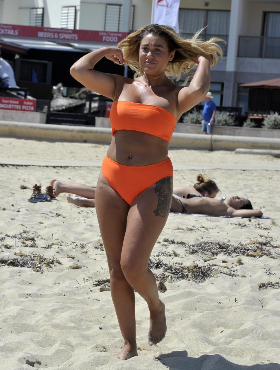 """Big Brother"" Ellie Young puts on busty display as she shows off cleavage in a bright orange bikini in Spain (October 2018)."