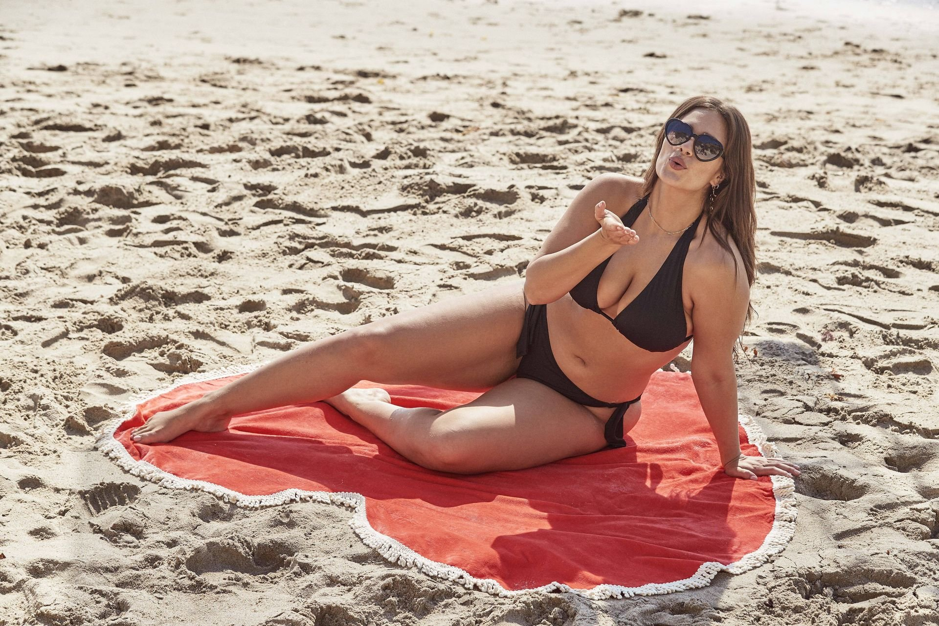 Ashley Graham showing off her new swimwear collection on a heart-shaped towel, 13-02-2019
